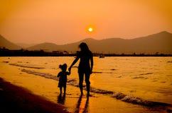 Silueta de la madre y del bebé que caminan en puesta del sol Foto de archivo libre de regalías