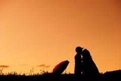Silueta de la madre y del hijo de A que juegan al aire libre en la puesta del sol Imagenes de archivo