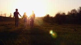 Silueta de la madre y del padre que caminan con su hija en la puesta del sol almacen de metraje de vídeo