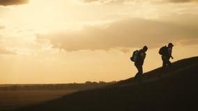 Silueta de la mano amiga entre el escalador dos dos caminantes encima de la monta?a, un hombre ayudan a un hombre a subir un esca almacen de video