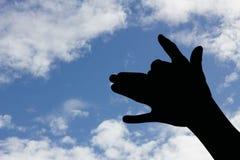 Silueta de la mano de la forma del perro en cielo azul Fotos de archivo