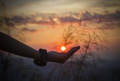 Silueta de la mano que sostiene el sol Fotos de archivo libres de regalías