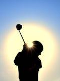 Silueta de la muchacha adolescente que hace pivotar a un club de golf Foto de archivo libre de regalías