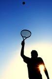 Silueta de la muchacha adolescente que sirve una pelota de tenis Foto de archivo libre de regalías