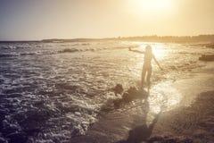 Silueta de la muchacha alegre en la playa en rayos del sol imagenes de archivo
