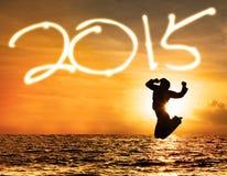 Silueta de la muchacha con el número 2015 en puesta del sol Imágenes de archivo libres de regalías