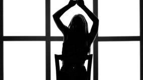 Silueta de la muchacha con el pelo que agita largo en profil en el fondo blanco con la ventana de la rejilla metrajes