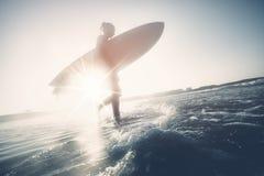 Silueta de la muchacha de la persona que practica surf Foto de archivo libre de regalías