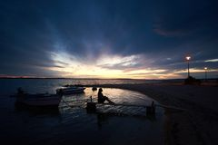 Silueta de la muchacha delgada que se sienta en el puente de madera estrecho en los pequeños barcos de motor en la puesta del sol fotografía de archivo