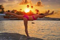 Silueta de la muchacha en la gimnasia de la puesta del sol de la playa imágenes de archivo libres de regalías