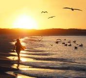 Silueta de la muchacha que camina abajo de la playa en la puesta del sol Foto de archivo libre de regalías