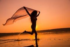 Silueta de la muchacha que corre en la playa Imagen de archivo