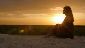 Silueta de la muchacha que disfruta de la puesta del sol que se sienta en la arena, figura de la mujer hermosa en armonía con la  metrajes