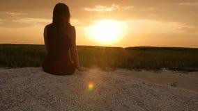 Silueta de la muchacha que disfruta de la puesta del sol que se sienta en la arena, figura de la mujer hermosa en armonía con la  almacen de metraje de vídeo