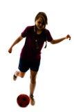 Silueta de la muchacha que juega a fútbol Fotos de archivo libres de regalías