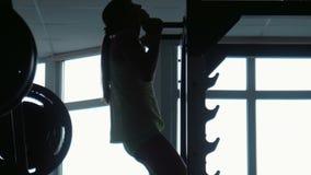 Silueta de la muchacha que levanta en una barra horizontal almacen de video