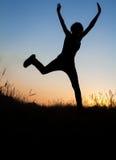 Silueta de la muchacha que salta en campo Imagenes de archivo