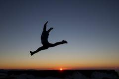 Silueta de la muchacha que salta en puesta del sol Imagenes de archivo