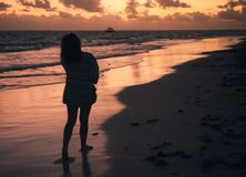Silueta de la muchacha que se coloca en la costa de Océano Atlántico Imagen de archivo libre de regalías