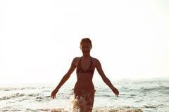 Silueta de la muchacha que se divierte en el mar Báltico que salpica ondas Fotos de archivo libres de regalías