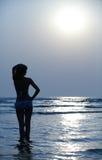 Silueta de la muchacha y de la puesta del sol azul Foto de archivo libre de regalías
