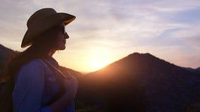 Silueta de la mujer adorable del viaje en sombrero y gafas de sol en el fondo de la montaña de la puesta del sol metrajes