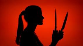 Silueta de la mujer asustadiza que sostiene la cuchilla aguda Cara femenina del ` s en perfil con el cuchillo en fondo rojo almacen de video