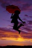 Silueta de la mujer con el salto del paraguas Imágenes de archivo libres de regalías