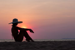 Silueta de la mujer con el sombrero que se sienta en fondo del mar Imagen de archivo