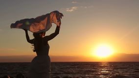 Silueta de la mujer con la bufanda en la playa en la puesta del sol