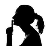 Silueta de la mujer con la muestra del silencio Fotos de archivo