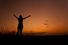 Silueta de la mujer con las manos en el cielo Fotografía de archivo