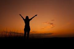 Silueta de la mujer con las manos en el cielo Imagen de archivo libre de regalías