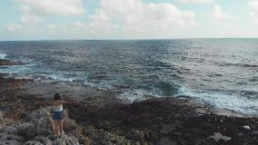 Silueta de la mujer con las manos extensas en aire en el acantilado rocoso a lo largo del océano con las ondas que golpean la cos