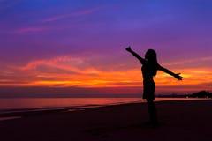 Silueta de la mujer con las manos para arriba mientras que se coloca en la playa del mar en fotos de archivo