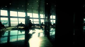 Silueta de la mujer con la maleta que camina a través de pasillo en el aeropuerto, cámara lenta, sol que brilla almacen de video