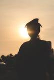 Silueta de la mujer con puesta del sol Fotos de archivo libres de regalías
