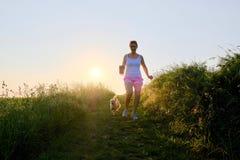 Silueta de la mujer con un perro que corre abajo de una trayectoria de la grava en la puesta del sol Imágenes de archivo libres de regalías