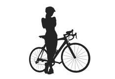 Silueta de la mujer con una bicicleta Foto de archivo