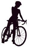 Silueta de la mujer con una bicicleta Imagenes de archivo