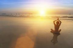 Silueta de la mujer de la yoga que hace la meditación Imagen de archivo libre de regalías