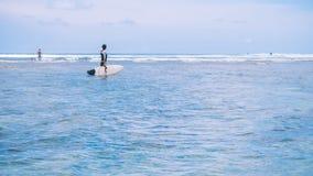 Silueta de la mujer del ajuste que va a practicar surf en el mar y que mira para agitar el borde en horizonte en la isla de Bali, imagenes de archivo
