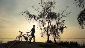 Silueta de la mujer del ciclista que camina con la bicicleta en la playa, estirando ejercicio