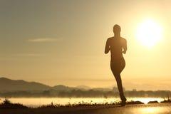 Silueta de la mujer del corredor que corre en la puesta del sol Imagen de archivo