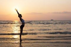 Silueta de la mujer del deporte en la playa Imagen de archivo