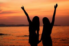Silueta de la mujer dos que se divierte en la playa del mar Imágenes de archivo libres de regalías