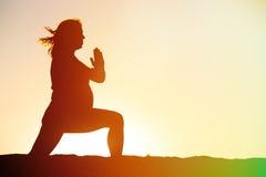 Silueta de la mujer embarazada que hace yoga en la playa Foto de archivo libre de regalías