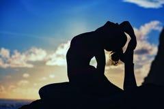 Silueta de la mujer en actitud de la yoga en la playa del mar de la puesta del sol Fotografía de archivo