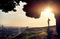 Silueta de la mujer en la opinión de la ciudad de la puesta del sol Imagen de archivo libre de regalías