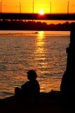Silueta de la mujer en la puesta del sol. Foto de archivo libre de regalías